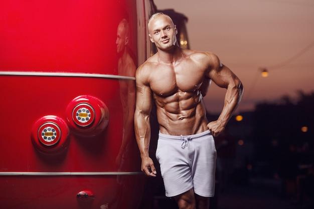 赤いバスの近くの通りでフィットネス運動男。ボディービルと健康の概念