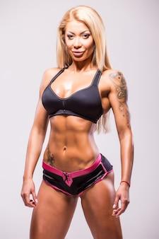 Женщина фитнеса атлетическая в бикини показывая мышцы. изолированные на белом