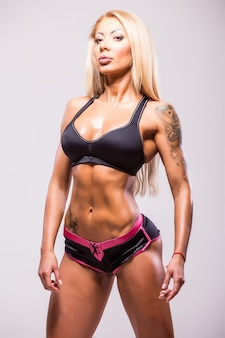 筋肉を示すビキニのフィットネスアスレチック女性。