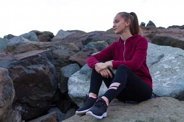 Fitness attractive woman in sneakers sitting on a stone, resting after a workout and looking into the distance at sunset. solitude with nature, sports and active lifestyle