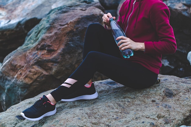 Fitness attractive woman in sneakers sitting on a stone