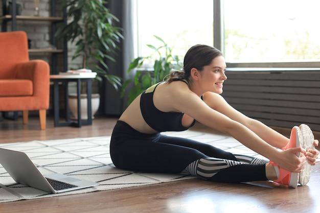 피트니스 아름다운 날씬한 여성이 거실에서 집에서 피트니스 스트레칭 운동을 하고 있습니다. 집에서 활동하기. 스포츠, 건강한 라이프 스타일.