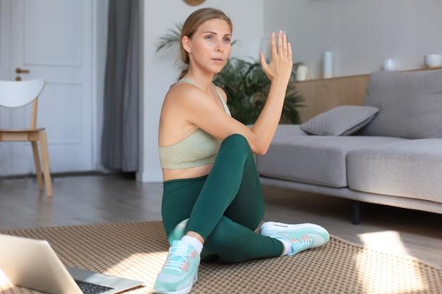 피트니스 아름다운 날씬한 여성이 거실에서 집에서 피트니스 스트레칭 운동을 하고 있습니다. 재택 활동에 머물기. 스포츠, 건강한 라이프 스타일.