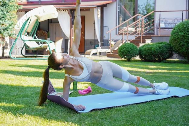 아름다운 날씬한 여성이 사이드 플랭크를 하고 노트북으로 온라인 자습서를 보고 야외 훈련을 하고 있습니다. 스포츠, 건강한 라이프 스타일.