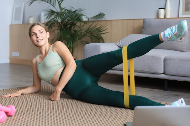 Fitness beautiful slim woman doing side plank with an elastic band and watching online tutorials on laptop.