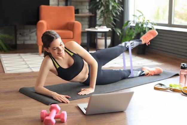 Фитнес красивая стройная женщина делает боковую планку с лентой сопротивления и смотрит онлайн-уроки на ноутбуке, тренируется в гостиной. оставайтесь дома.