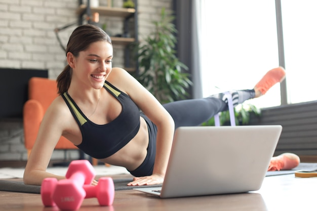 Fitness beautiful slim woman doing side plank with resistance band and watching online tutorials on laptop, training in living room. stay at home activities.