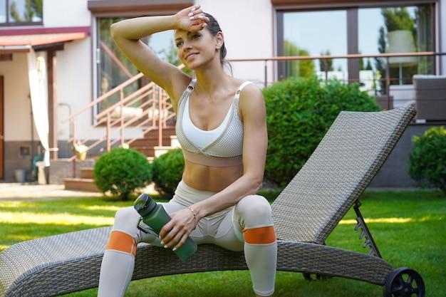 Красивая стройная женщина фитнеса сидит с бутылкой воды на открытом воздухе, отдыхая после тренировки. здоровый образ жизни.