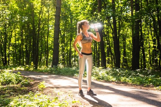 피트니스 아름다운 여자 식수와 공원에서 여름 더운 날에 운동 후 땀