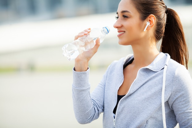 Fitness. beautiful woman drinking water and listen to music after running