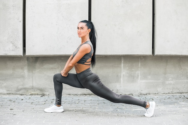 Fitness beautiful woman model in stylish clothes doing stretching muscles exercises on city streets. sporty fashion girl in leggings trains outdoors.
