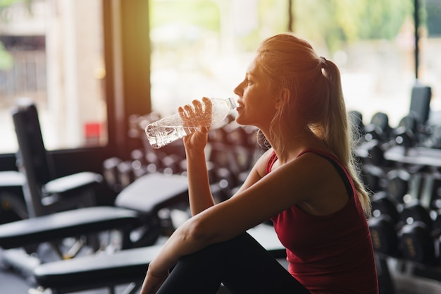 Fitness beautiful woman siting and resting after workout in fitness studio while drinking energy water