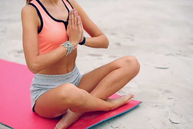 Fitness beautiful woman training her body at the beach