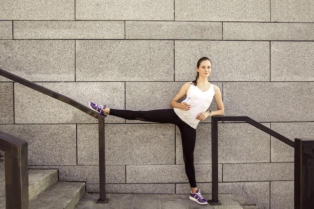 도시에서 운동한 후 얼굴에 주근깨가 있는 아름다운 여성이 물을 마시고 땀을 흘리고 있습니다. 운동 후 여성 운동 선수입니다. 카메라를 보고 웃고.