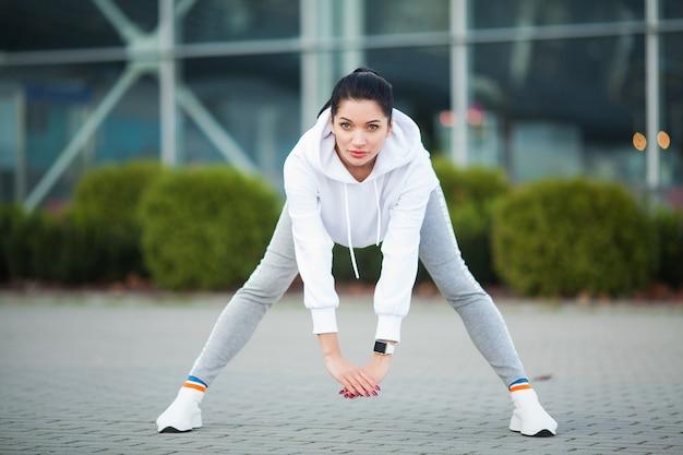 フィットネス。公園で運動する美しい若い女性-スポーツと健康的なライフスタイルの概念。
