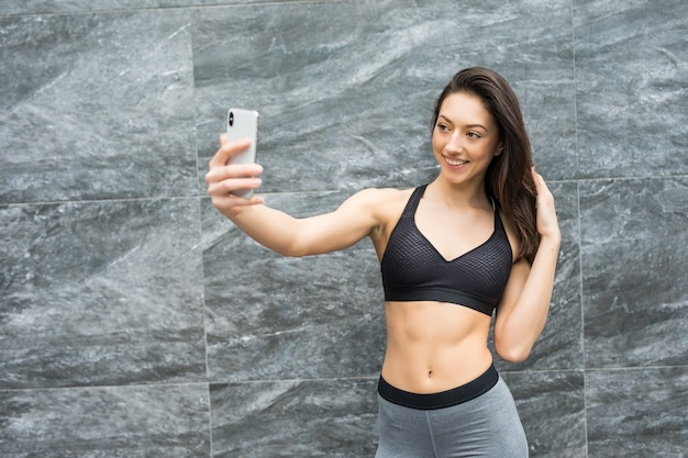 Donna di bellezza fitness davanti al muro all'aperto prende selfie con lo smartphone in città dopo l'allenamento da condividere nei social network