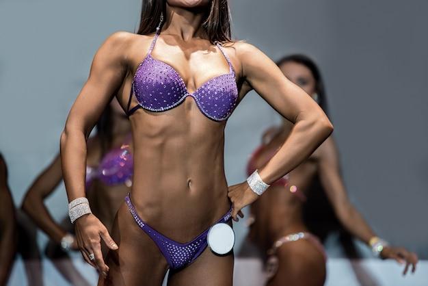 Fitness bikini athlete's lean torso. woman demonstrating fit torso. beautiful figure and tanned skin. perfect female body.