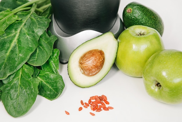 Fitness blender with a set of healthy products, apple avocado spinach