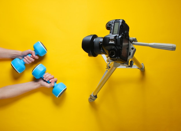 Fitness blogger. woman holding plastic dumbbells with her hands and blogging with camera on tripod. top view