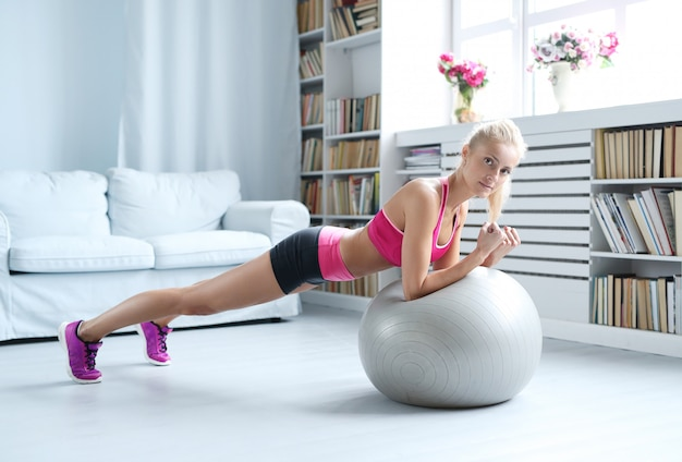 Fitness blonde woman doing stretches with her exercise ball at home