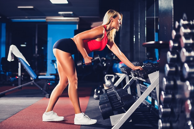 Fitness blonde woman posing and exercising with dumbbell