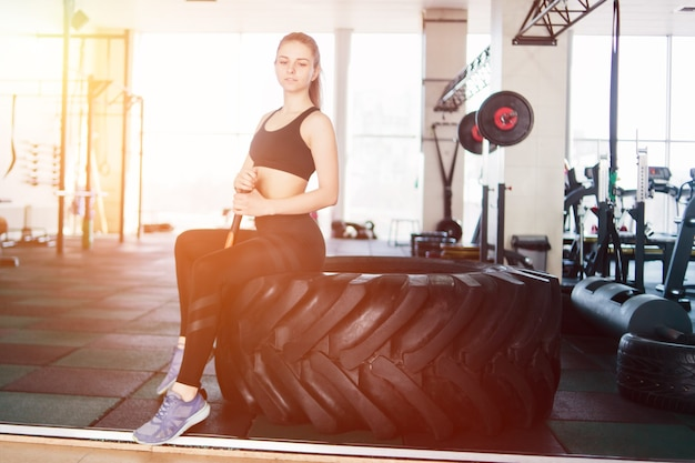 Fitness blonde woman sitting on a big black wheel for funcional training and holding a hammer in her hands in gym