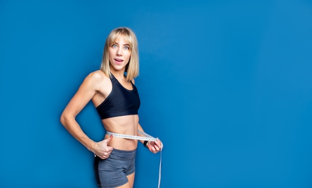 Fitness blonde woman in sportwear with tape measure on blue space. slim, fit, liposuction concept. copyspace.
