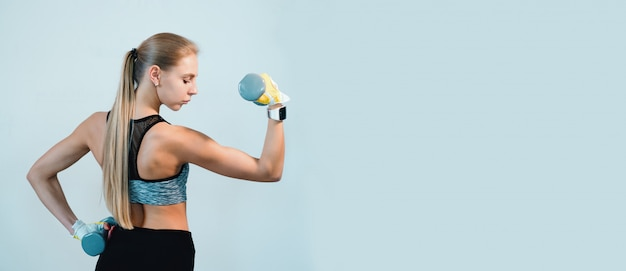 Fitness blonde woman standing with dumbbells back sport