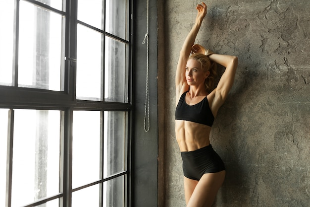 Fitness blondie woman standing near the wall and window