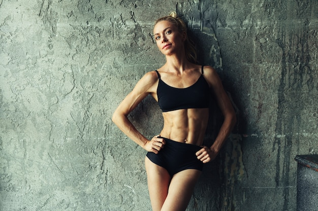Fitness blondie woman standing near the wall