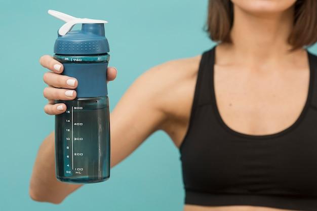 Bottiglia di forma fisica piena di acqua e donna