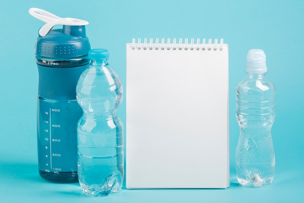 Fitness bottle of water and copy space notepad