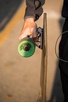Fitness boy holding skateboard