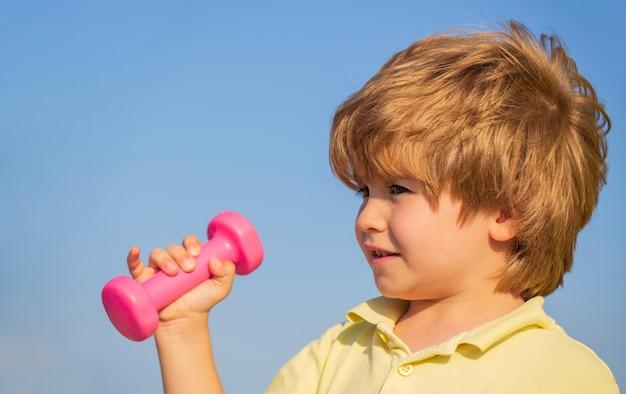 フィットネスの子供。ダンベルを持つスポーティな男の子。フィットネス、健康、エネルギー。元気な男の子はダンベルで運動をします。ダンベルで運動する子供。小さな子供のためのスポーツ。健康的な生活様式。