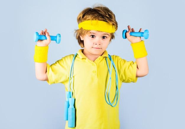 フィットネスの子供たち。縄跳びとダンベルのスポーツウェアのスポーティな男の子。子供のスポーツマン。