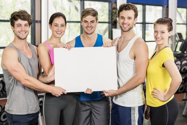 Fitness class holding a white card in gym
