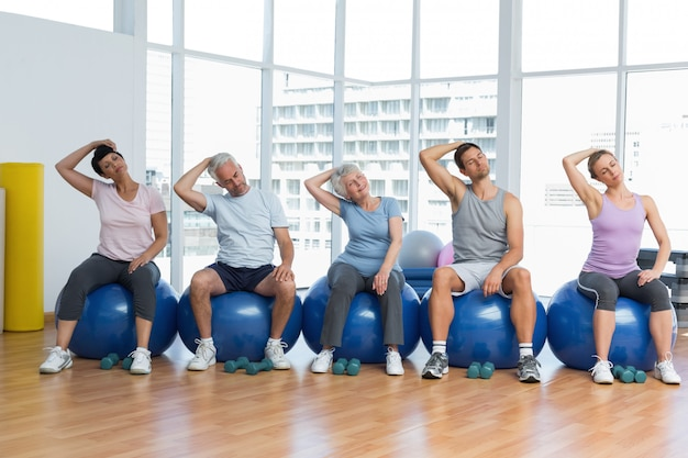 Fitness class sitting on exercise balls and stretching neck in a bright gym