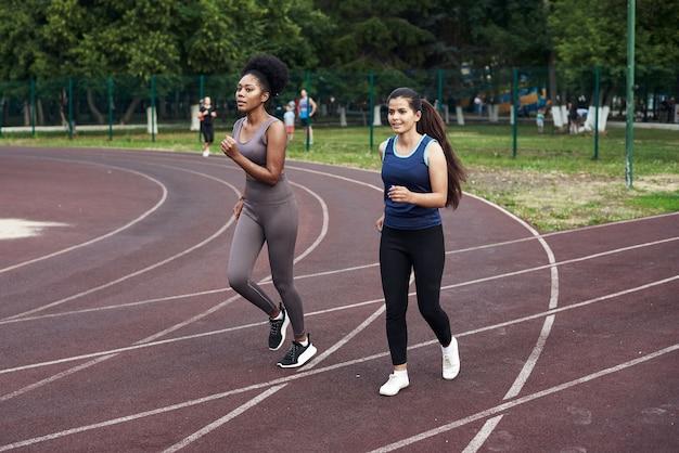 Занятия фитнесом на ул. милые подружки бегают по спортивной дорожке на стадионе.