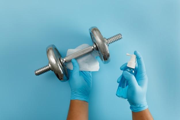 Фитнес-чистка тренажерного зала вирус covid 19 с использованием спиртового спрея антивирусная концепция тренировка из дома оставайтесь в безопасности