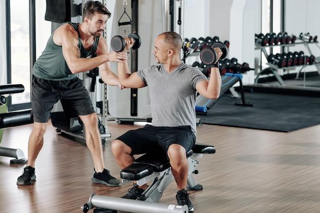 混血の若い男に重いダンベルを使って運動する方法を説明するフィットネスコーチ
