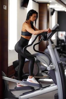 フィットネスコーチがステップマシンに取り組んでいて、スポーツスーツで彼女の姿を見せている