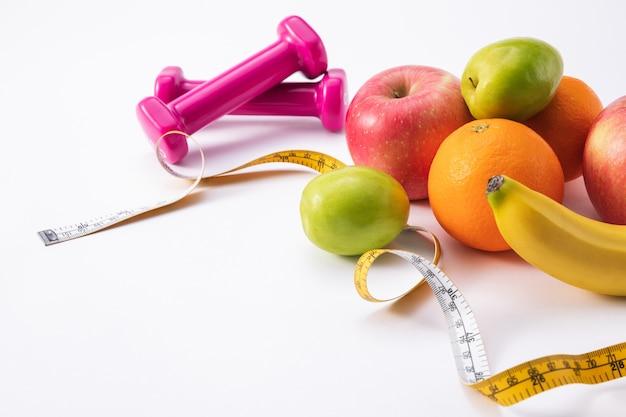 Composizione fitness con manubri rosa, frutta fresca e metro a nastro su una superficie bianca