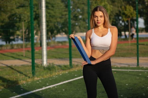 フィットネスのコンセプト:スポーツグラウンドで抵抗バンドを使ってタトゥーを温めている素晴らしいブロンドのフィットの女性。テキスト用のスペース