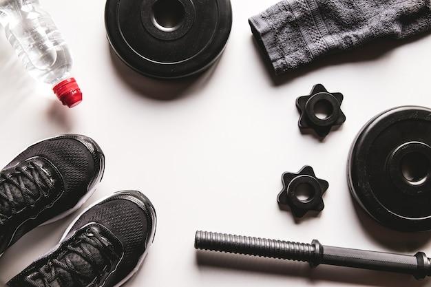 スニーカー、水筒とフィットネスコンセプトの背景。上面図