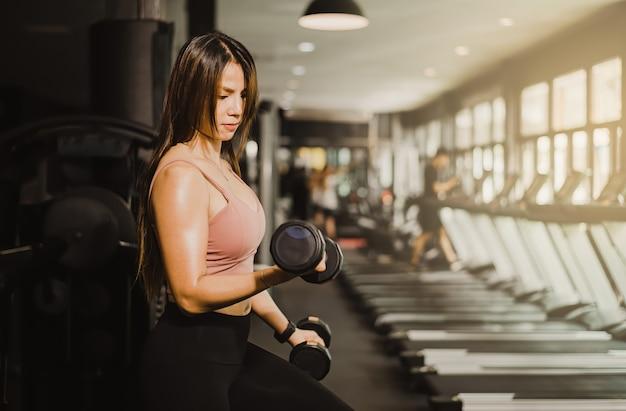 Концепция фитнеса, гантели красивой азиатской женщины поднимаясь, чтобы нарастить мышцы в тренажерном зале.