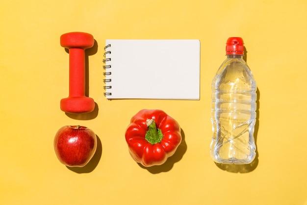 Концепция фитнеса. коллекция свежих фруктов с гантелями и бутылкой с водой на желтом фоне.