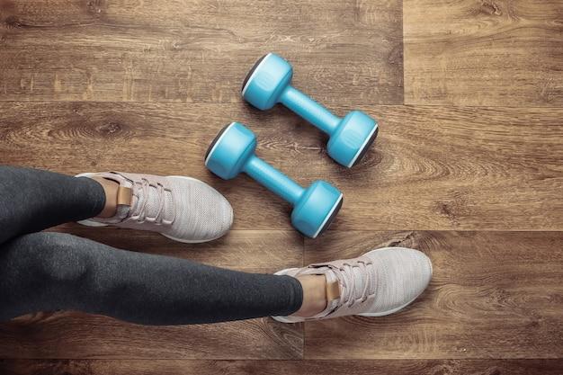 フィットネスのコンセプト。レギンスやスポーツシューズの女性の脚は、ダンベルを持って床に座っています。