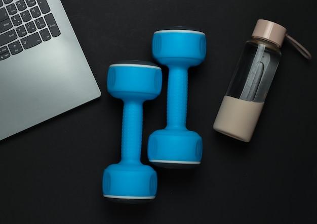 フィットネスのコンセプト。コーチングの専門家のためのオンライントレーニング。ノートパソコン、ダンベル、黒の背景に水のボトル。上面図