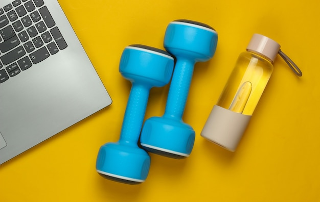 フィットネスのコンセプト。コーチングの専門家のためのオンライントレーニング。ノートパソコン、ダンベル、黄色の背景に水のボトル。上面図