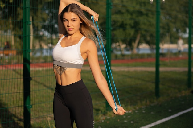 Fitness concept: pretty blonde fit woman with a tattoo warming with a resistance band at the sports ground. space for text